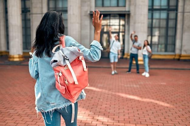 Śliczny afroamerykanin studentka z różowym plecakiem macha do grupy studentów w pobliżu kampusu.