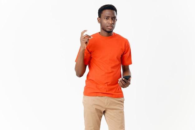 Śliczny afroamerykanin w koszulce i szortach z telefonem komórkowym na jasnym tle