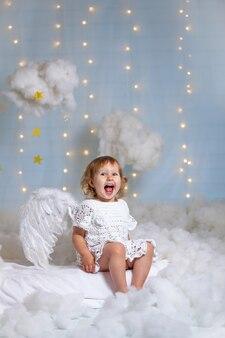 Śliczny aniołek siedzi w chmurach śmiejąc się radośnie