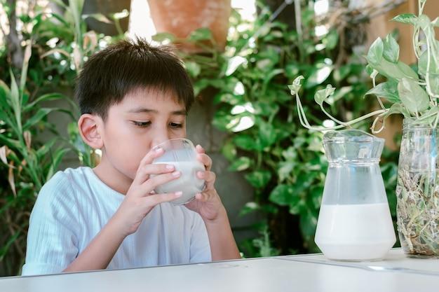Śliczny azjatycki chłopak w białej koszulce pije szklankę mleka.
