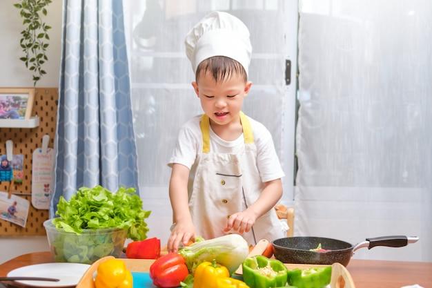 Śliczny azjatycki chłopiec dziecko jest ubranym szefa kuchni kapelusz i fartucha ma zabawy narządzanie, gotuje zdrowego jedzenie w kuchni