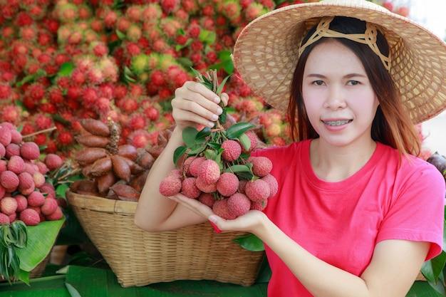 Śliczny azjatycki dziewczyna kupiec z jej owoc.