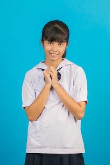Śliczny azjatycki dziewczyna uczeń robi prośba gestowi na błękicie.