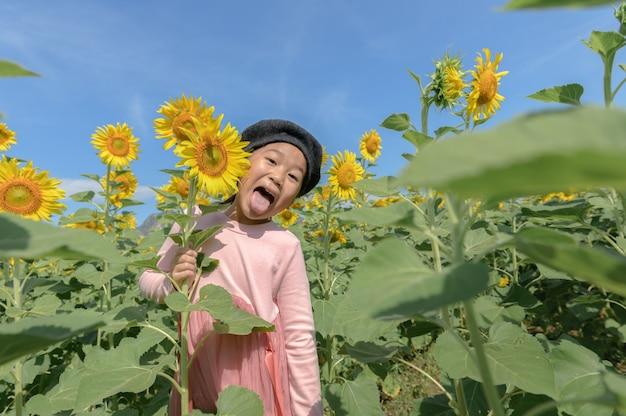 Śliczny azjatycki dziewczyna uśmiech z słonecznikowym kwiatem