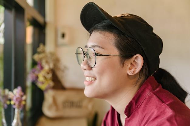 Śliczny azjatycki gruby nastoletni uśmiech z szkłami uśmiechniętymi i patrzeje z okno