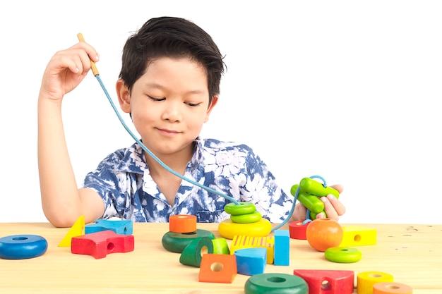 Śliczny azjatykci chłopiec jest bawić się kolorową drewnianą blokową zabawkę