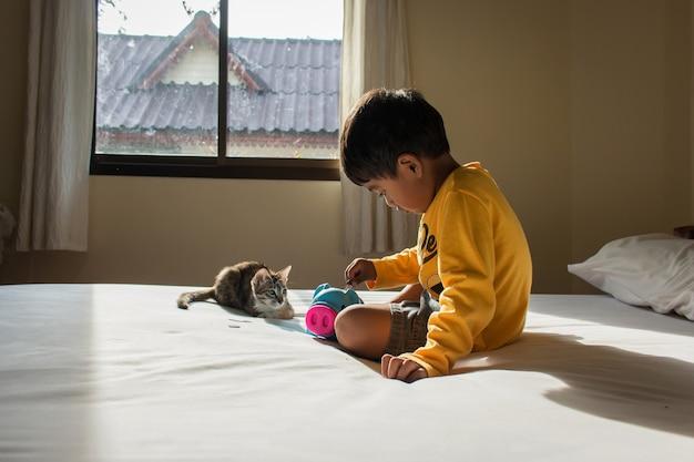 Śliczny azjatykci chłopiec oszczędzania pieniądze w prosiątko banku
