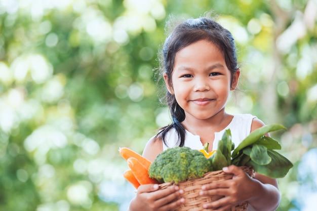 Śliczny azjatykci dziecko dziewczyny mienia kosz warzywa przygotowywa dla gotować z jej rodzicem