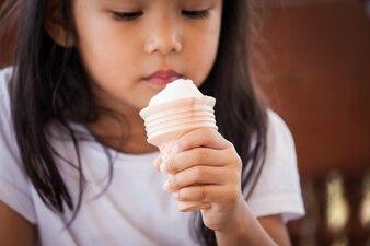 Śliczny azjatykci małej dziewczynki ręki mienia lody rożek w rocznika koloru brzmieniu