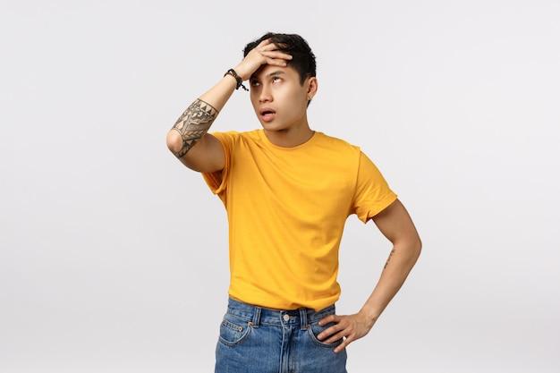 Śliczny azjatykci mężczyzna uderza pięścią w czoło w żółtej koszulce