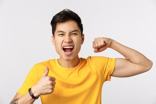 Śliczny azjatykci mężczyzna w żółtej koszulce pokazuje mięsień i kciuk up