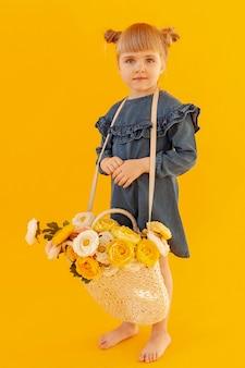 Śliczny berbeć jest ubranym kwiatu kosz