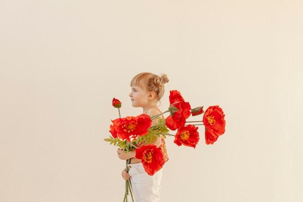 Śliczny berbeć trzyma dużych kwiaty