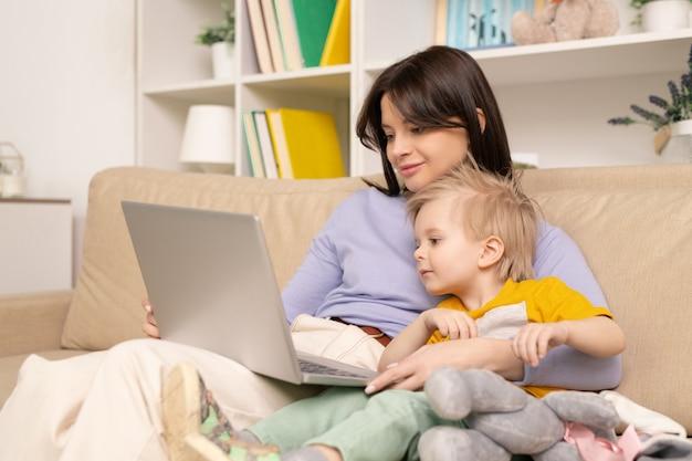 Śliczny blond chłopiec i jego ładna mama oglądają film lub kreskówkę na laptopie, relaksując się na wygodnej kanapie w salonie