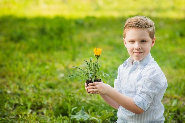 Śliczny blond chłopiec mienia kwiat w ogródzie