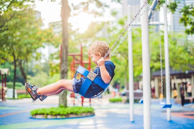 Śliczny blond chłopiec na huśtawce w parku