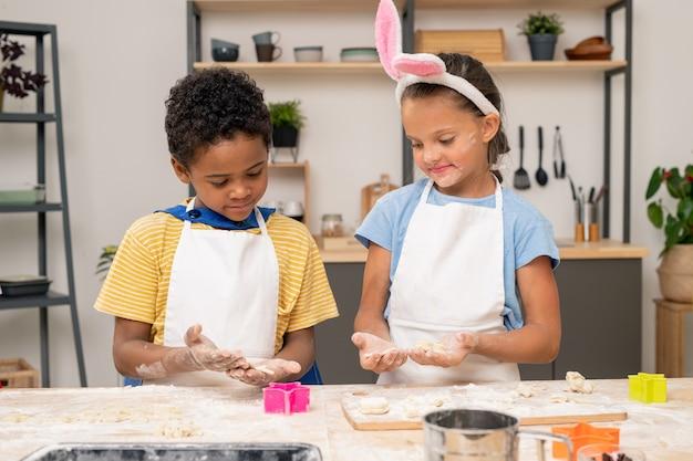 Śliczny blond chłopiec toczący domowe ciasto na drewnianym stole z mamą stojącą w pobliżu podczas wspólnego gotowania