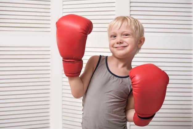 Śliczny blond chłopiec w czerwonych rękawicach bokserskich. pojęcie sportu