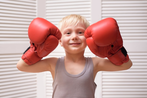Śliczny blond chłopiec w czerwonych rękawicach bokserskich. sport