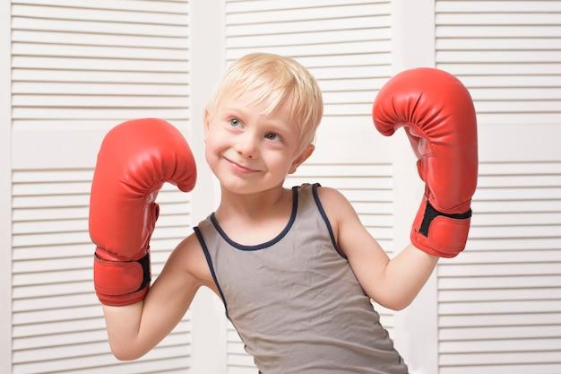 Śliczny blond chłopiec w czerwonych rękawicach bokserskich.