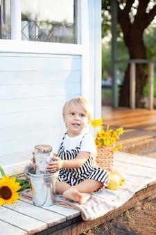 Śliczny blond chłopiec w kombinezonie biały t-shirt siedzi na ganku drewnianego domu w jesienny dzień i gra. odpoczywaj w naturze. koncepcja dzieciństwa. żniwny. mały rolnik. zdrowy styl życia rodziny