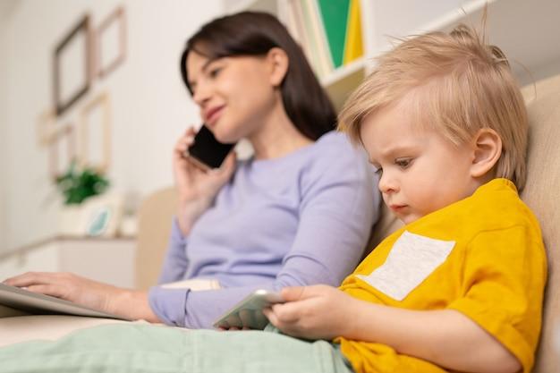 Śliczny blond chłopiec ze smartfonem ogląda kreskówki online, podczas gdy jego matka rozmawia przez telefon i pracuje zdalnie w kwarantannie