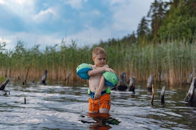 Śliczny blond kaukaski chłopiec stojący w stawie z rafami dostosowującymi opaski na ramionach