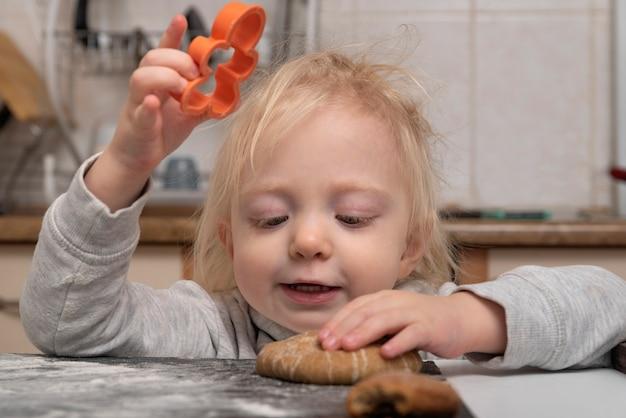 Śliczny blond maluch pomaga gotować ciasteczka