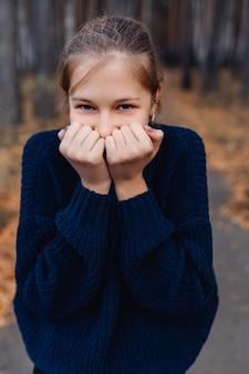 Śliczny blondynka nastolatek w jesień parku. młoda dziewczyna stoi w lesie