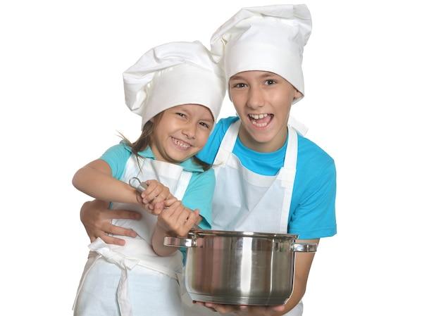 Śliczny brat i siostra pozują w mundurach szefa kuchni