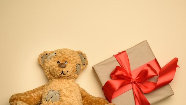 Śliczny brązowy miś obok pudełka z prezentem przewiązanym czerwoną jedwabną wstążką, beżowe tło, miejsce na kopię