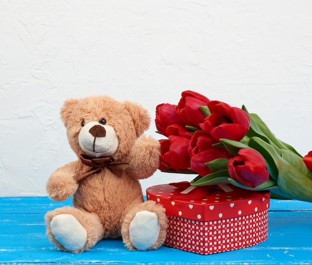 Śliczny brązowy miś siedzi na niebieskim drewnianym stole, bukiet czerwonych tulipanów, czerwone pudełko