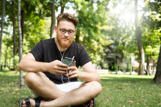 Śliczny brodaty rudzielec młody człowiek słucha muzyka na smartphone w hełmofonach podczas gdy siedzący w parku.