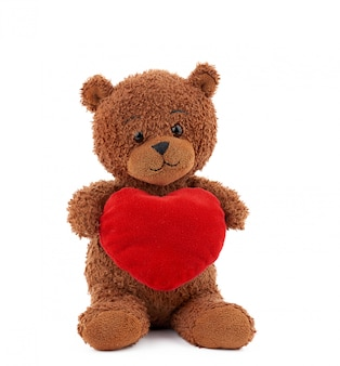 Śliczny brown miś trzyma dużego czerwonego serce