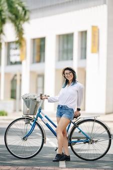 Śliczny całkiem młoda chinka stojąca na drodze obok swojego roweru i uśmiechnięta