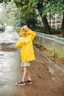 Śliczny chłopak w żółtym płaszczu przeciwdeszczowym i sandałach bawi się biegając po kałużach po mieście. skakać przez błotniste kałuże. szczęśliwe i beztroskie dzieciństwo