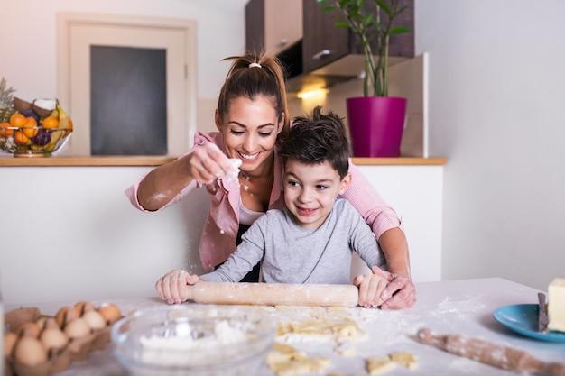 Śliczny chłopczyk i jego piękna mama w fartuchach uśmiechają się podczas ugniatania ciasta w kuchni