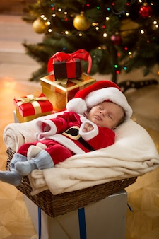 Śliczny chłopczyk w stroju świętego mikołaja śpi pod choinką
