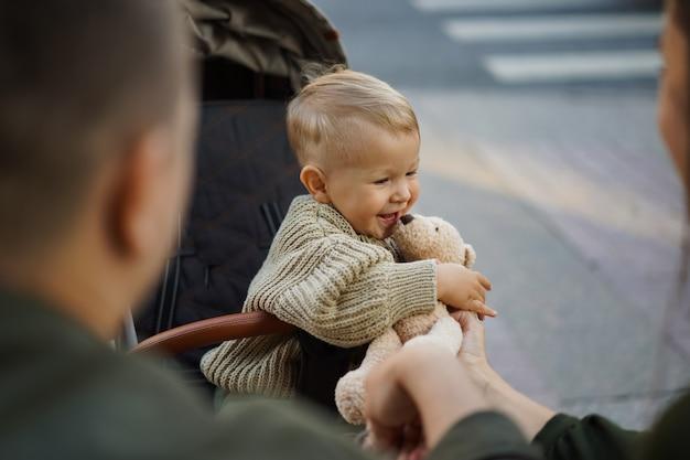 Śliczny chłopczyk w wózku trzymający pluszowego misia przejście dla pieszych z zebrą na tle obrazu z ...