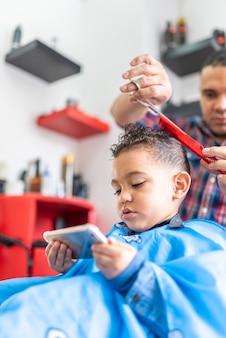Śliczny chłopiec dostaje ostrzyżenie w fryzjerze. pojęcie piękna.