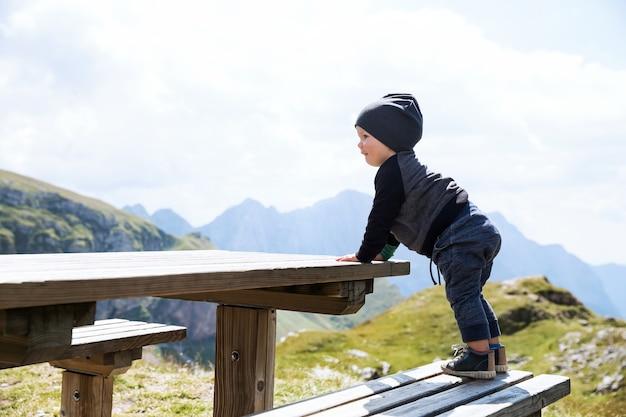 Śliczny chłopiec dziecko odkrywa i patrzy na widok na góry przy drewnianym stole