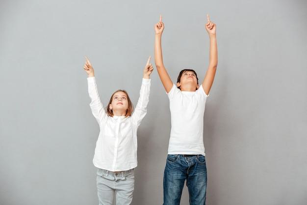 Śliczny chłopiec i dziewczynka stoją i wskazują w górę