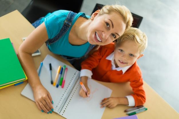 Śliczny chłopiec i jego mama siedzą przy biurku w biurze i trzymają ołówki
