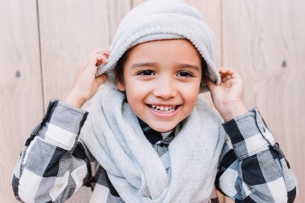 Śliczny chłopiec kładzenie na zimy nakrętce