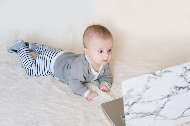Śliczny chłopiec lying on the beach i patrzeć w laptop