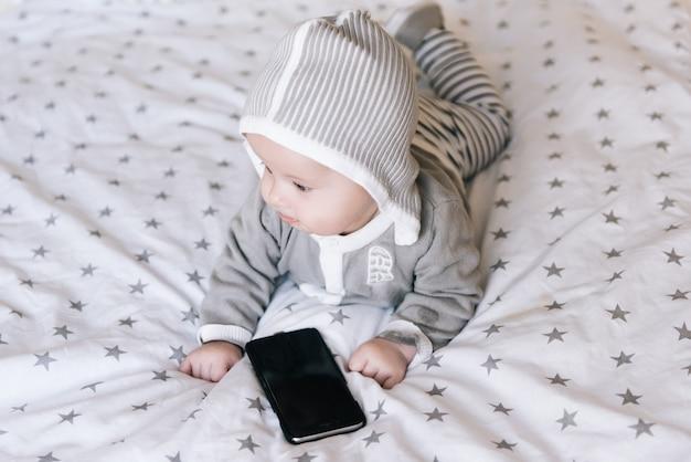Śliczny chłopiec lying on the beach na jego żołądku i patrzeć w telefon, selekcyjna ostrość