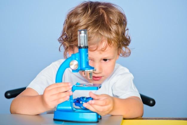 Śliczny chłopiec maluch bawi się z mikroskopową koncepcją edukacji i czytania