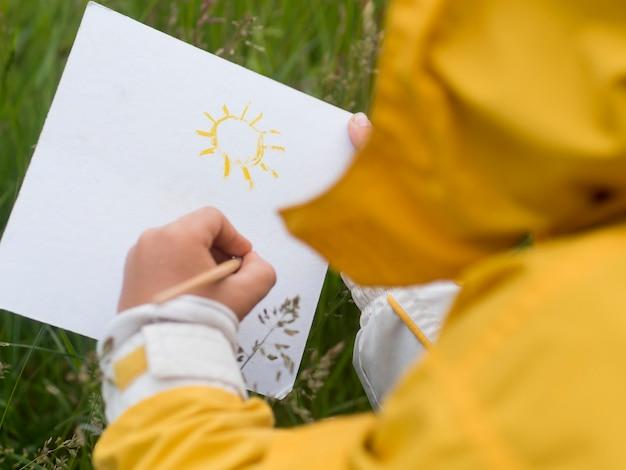 Śliczny chłopiec maluje nad ramieniem w płaszczu przeciwdeszczowym