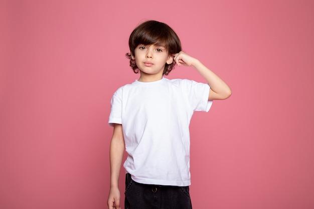 Śliczny chłopiec mały w białym t-shircie i niebieskich dżinsach na różowym biurku