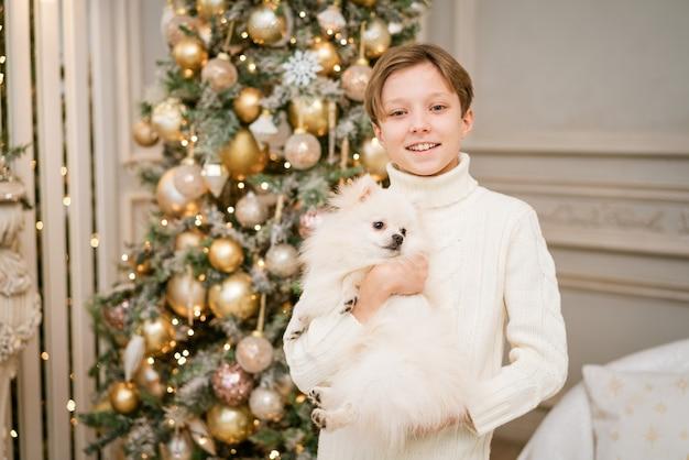 Śliczny chłopiec na choince z psem w oczekiwaniu na wesołych świąt szczęśliwy chłopiec i pies przytula...